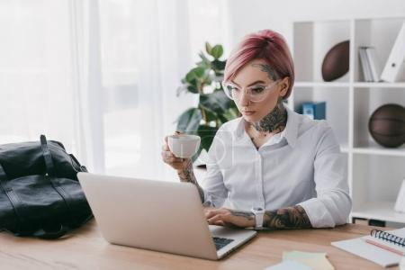 young tattooed businesswoman holding cup of coffee and using laptop in office