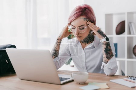 stressed young businesswoman using laptop at workplace