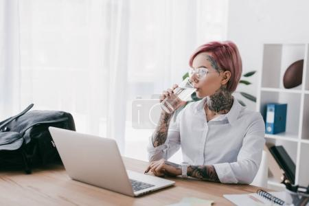Photo for Young businesswoman with tattoos drinking water and using laptop at workplace - Royalty Free Image