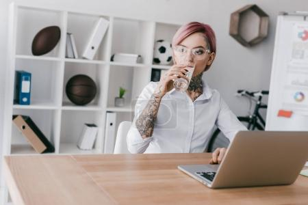 young tattooed businesswoman in eyeglasses drinking water while using laptop in office