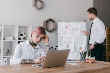 young businesswoman using laptop while businessman working with whiteboard in office