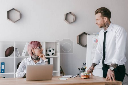 young businessman and businesswoman looking at each other in office