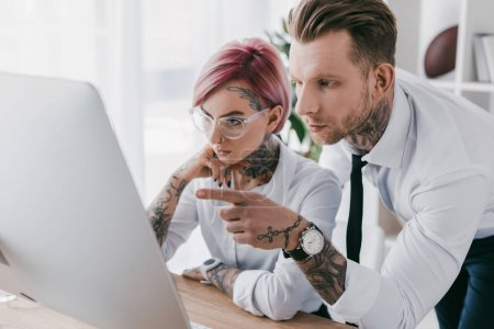 young tattooed business people in formal wear working with desktop computer in office