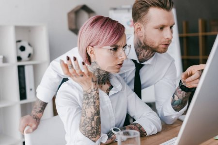 young tattooed colleagues in formal wear working with desktop computer in office