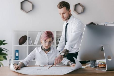 young tattooed business people in formal wear working with blueprint in office