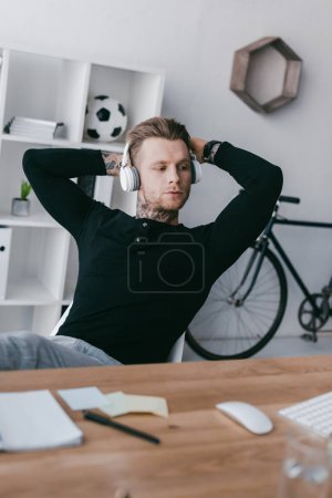 handsome young tattooed man in headphones sitting with hands behind head at workplace