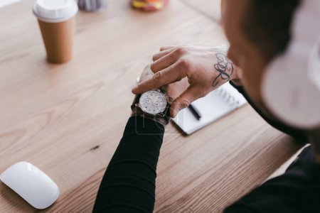 selective focus of young businessman checking wristwatch at workplace