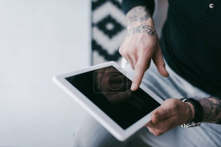 cropped shot of businessman with tattoos using digital tablet with blank screen