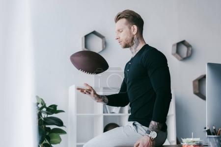 young businessman throwing rugby ball while sitting on table in office