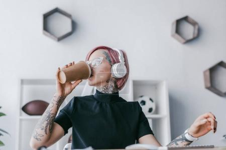Photo for Young businesswoman in headphones drinking coffee from paper cup at workplace - Royalty Free Image