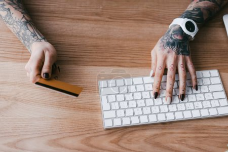 cropped shot of woman with tattoos holding credit card and typing on keyboard