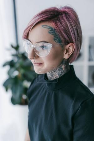 smiling young businesswoman with tattoos wearing eyeglasses and looking away