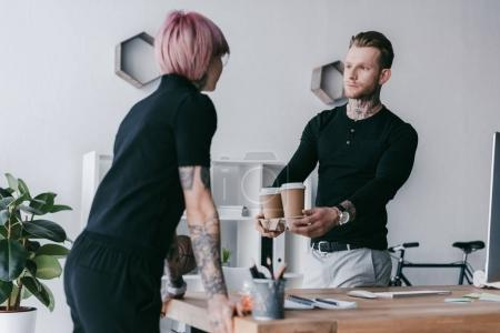 handsome young businessman giving paper cups to female colleague in office