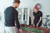 young tattooed colleagues playing foosball in office