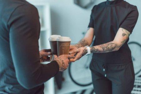 Photo pour Recadrée tir des collaborateurs détenant les gobelets en papier avec du café pour aller - image libre de droit