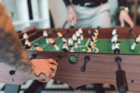 selective focus of colleagues playing table football in office