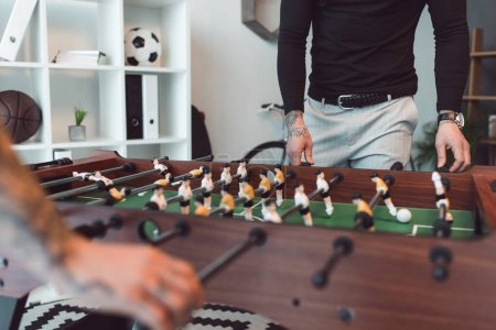 cropped shot of people playing table football in office