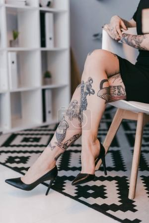 cropped shot of young businesswoman with tattoos sitting on chair in office