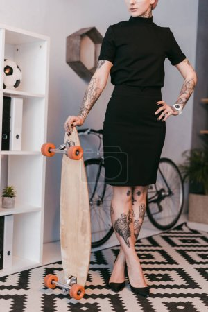 cropped shot of young businesswoman standing with skateboard in office