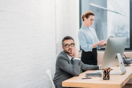 bored businessman working with his colleague in modern office
