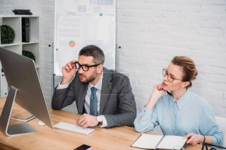 serious businesspeople working with computer together at modern office