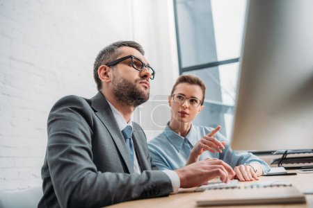 businesspeople working with computer together at modern office