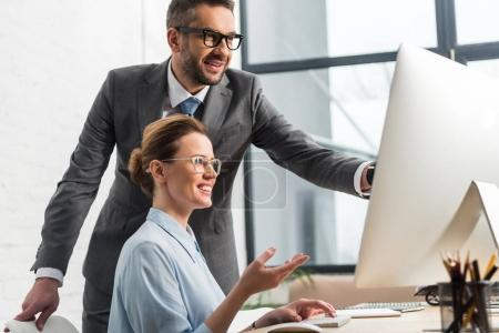 happy successful business partners working with computer together