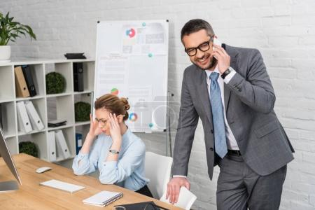 businessman talking by phone while his annoyed colleague trying to work