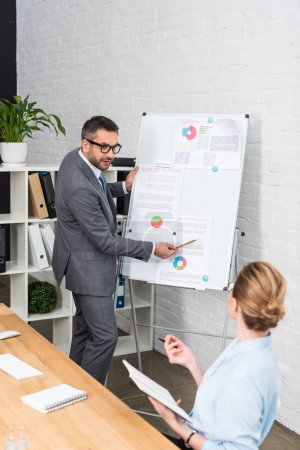 happy businessman making presentation with whiteboard for colleague at office