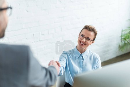 businesswoman shaking hand of colleague while sitting at workplace
