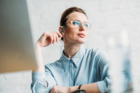 Photo for Attractive businesswoman sitting at workplace in office and looking away - Royalty Free Image