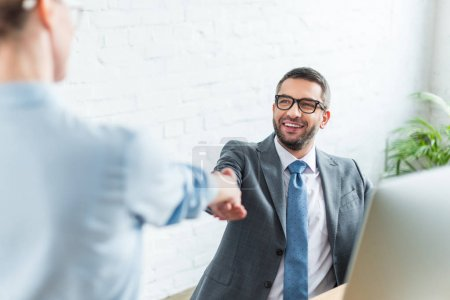 businessman shaking hand of colleague while sitting at workplace