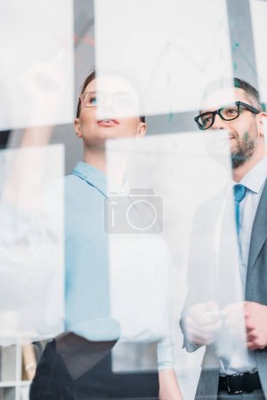 bottom view of businesspeople drawing graphs on glass presentation board
