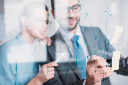 young businesspeople drawing graphs on glass presentation board