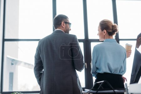 rear view of businesspeople having conversation at office and drinking coffee