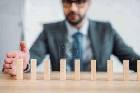 close-up shot of businessman assembling wooden blocks in row on worktable, dominoes effect concept