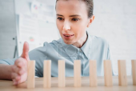 close-up shot of businesswoman assembling wooden blocks in row on worktable, dominoes effect concept