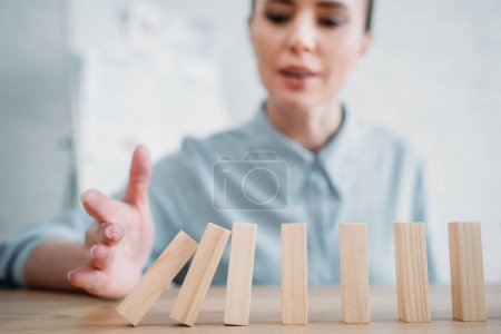 close-up shot of businesswoman with falling wooden blocks in row on table, dominoes effect concept