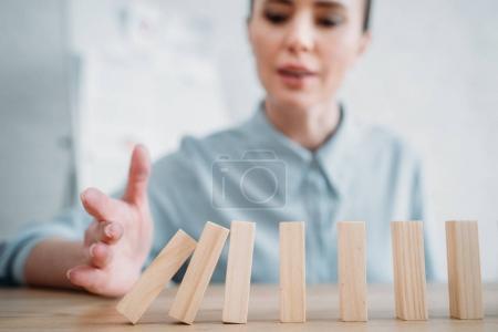 gros plan de femme d'affaires avec la chute des blocs de bois en ligne sur la table, l'effet dominos concept