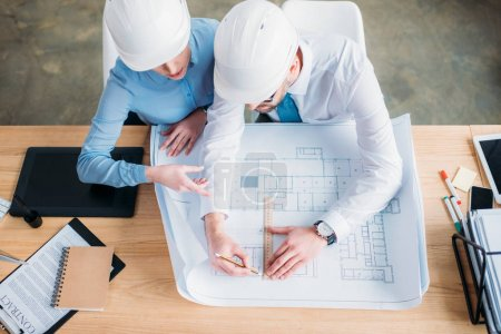 high angle view of architects working with building plan together at office
