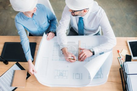 high angle view of experienced architects working with building plan at office