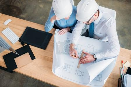 high angle view of architects in hard hats working with building plan at office