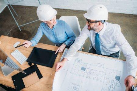 Photo pour Vue d'angle élevé des heureux architectes travaillant à la construction de plan au bureau - image libre de droit