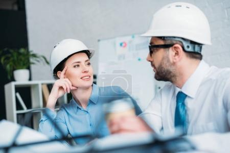 architects in hard hats talking about work at office