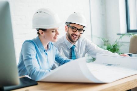 Photo pour Architectes souriants travaillant avec le plan de construction au bureau - image libre de droit
