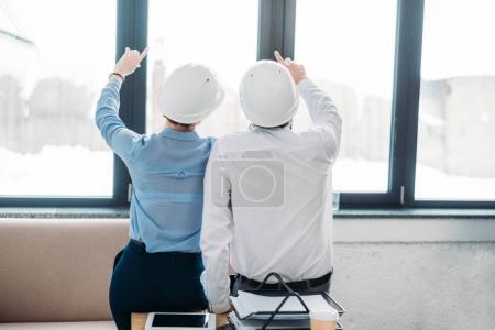 Photo pour Vue arrière des architectes pointant vers le haut par la fenêtre du bureau - image libre de droit