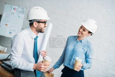 architects with paper cups of coffee talking at office