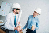 architectes avec les gobelets en papier de café parler au bureau