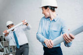 happy architects fighting with rolled building plans at office