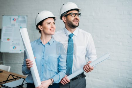 happy architects standing at modern office with building plans and looking away